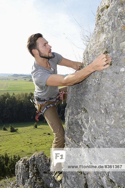 Mann klettert auf einem Felsen