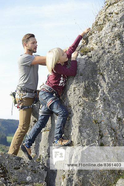 Vater und Sohn klettern auf einem Felsen