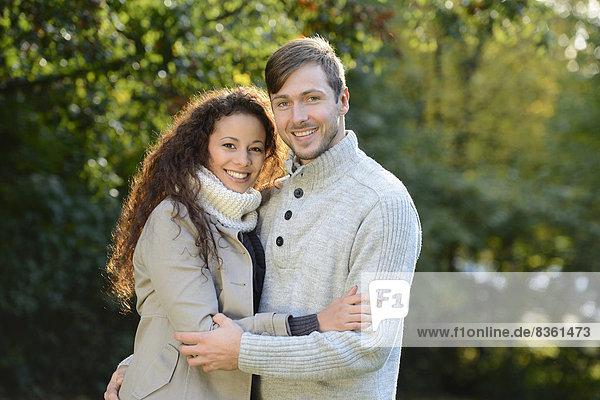 Lächelndes Paar umarmt sich im Herbst