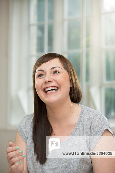 Young woman looking up and laughing