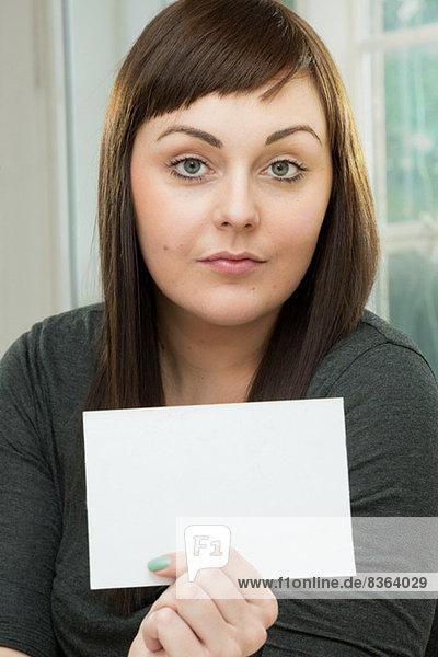 Seriöse junge Frau mit einer leeren Karte