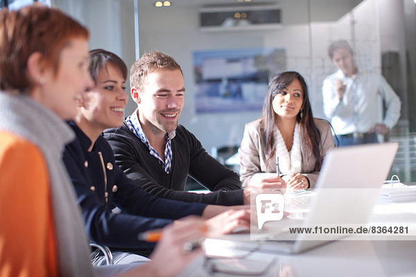 Geschäftsleute  die Laptop-Computer betrachten  lächelnd