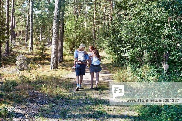 Eltern geben Töchtern Huckepack durch den Wald zurück
