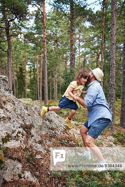 Vater hebt Tochter aus dem Fels