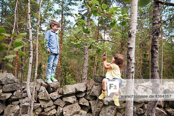 Mädchen auf der Wand sitzend fotografiert den Jungen