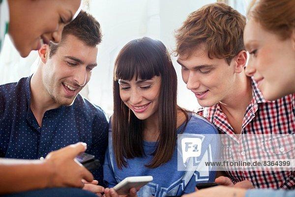 Group of five friends using smartphones