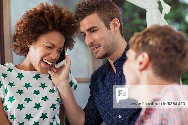 Frau auf dem Smartphone lacht mit männlichen Freunden