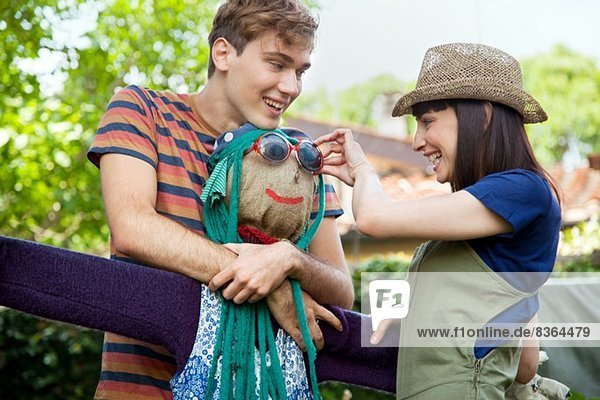 Couple putting sunglasses on scarecrow