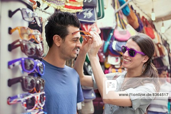 Young couple trying on sunglasses  San Lorenzo market  Florence  Tuscany  Italy