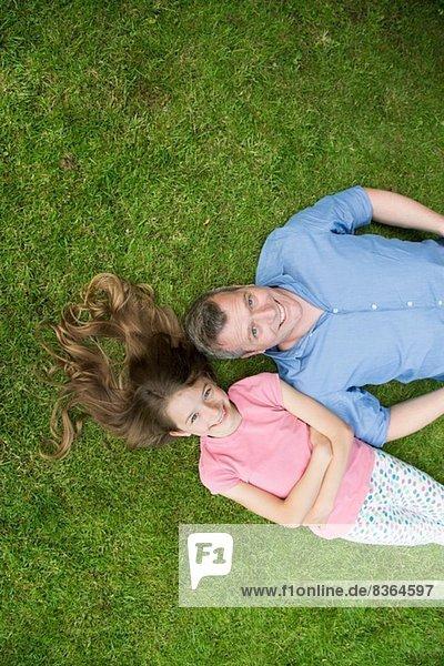 Vater und Tochter auf Gras liegend