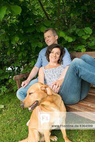 Erwachsenes Paar sitzt auf einer Gartenbank mit Hund