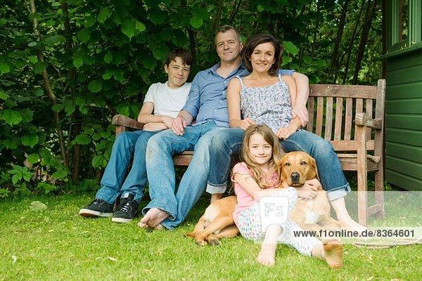 Porträt einer Familie mit zwei Kindern auf einer Gartenbank mit Hund