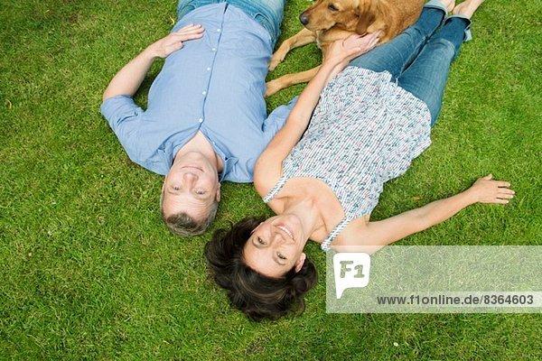 Porträt eines erwachsenen Paares auf Gras mit Hund
