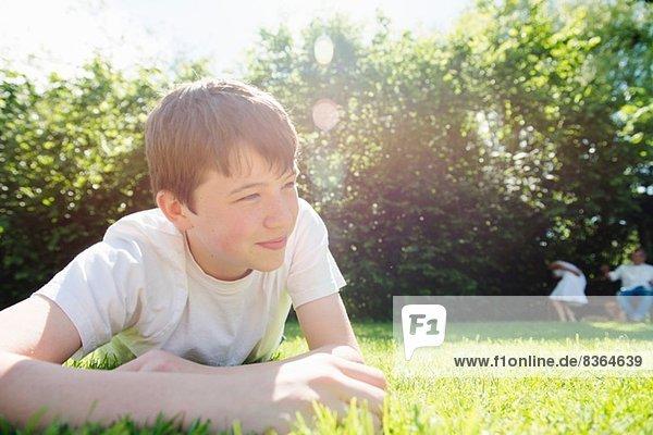 Portrait of teenage boy lying on grass  looking away