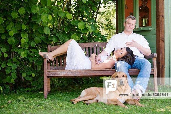 Portrait eines reifen Paares auf einer Gartenbank mit Hund