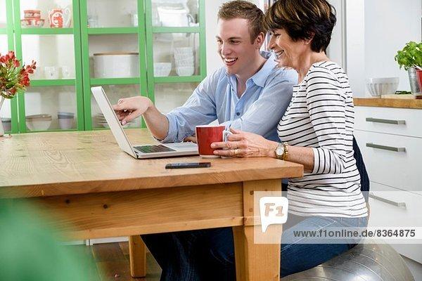 Sohn lehrt Mutter  Laptop zu benutzen