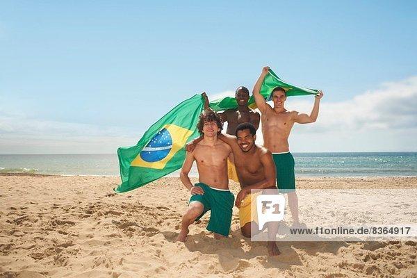 Freunde posieren mit brasilianischer Flagge am Strand