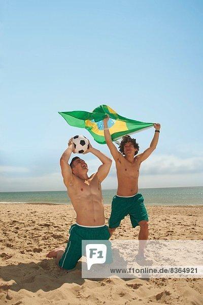 Männer mit brasilianischer Flagge am Strand