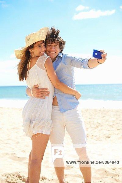 Paar Selbstfotografie mit Handy am Strand
