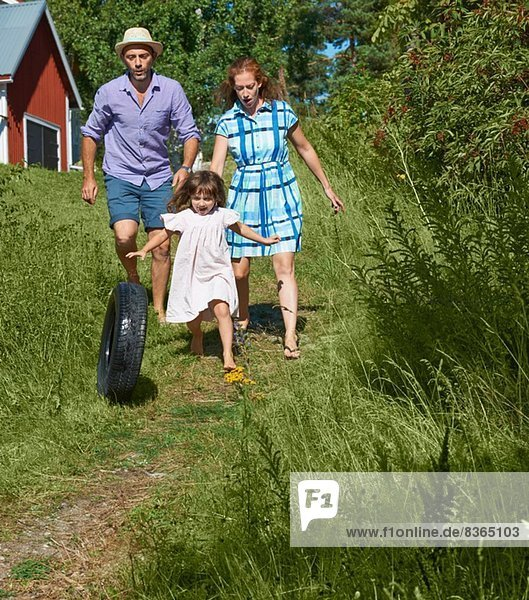 Eltern und Mädchen rollender Reifen auf dem Weg  Utvalnas  Gavle  Schweden