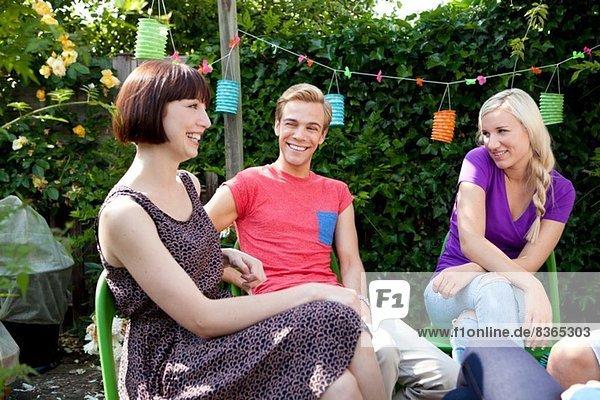 Junge erwachsene Freunde im Garten plaudern