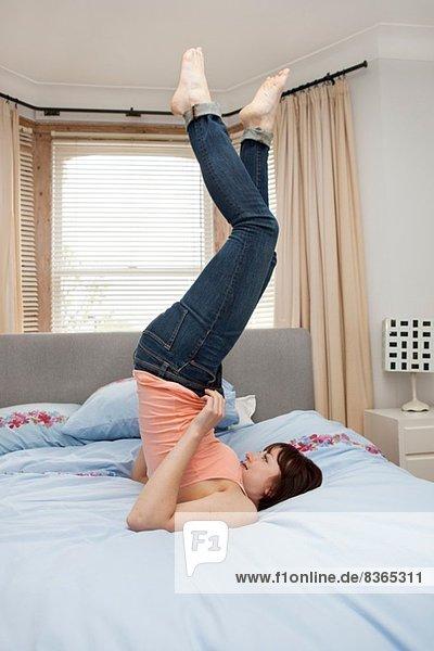 Junge Frau kämpft mit dem Reißverschluss der Jeans im Bett
