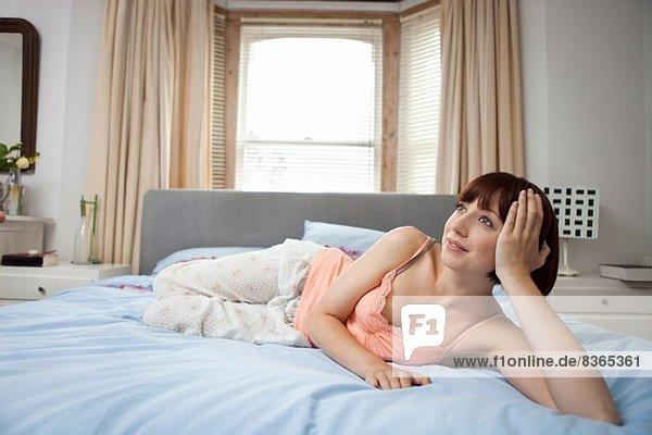 Junge Frau auf dem Bett liegend träumend