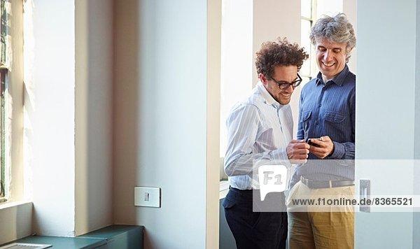 Zwei Männer mit Handy  die lachen.