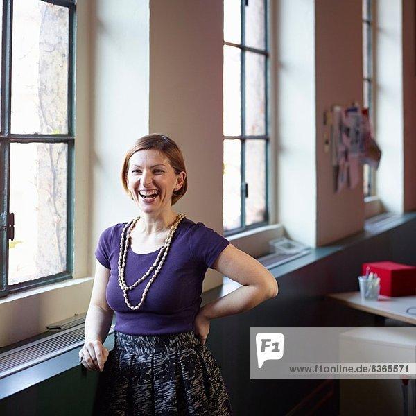 Mittlere erwachsene Frau am Fenster  lachend