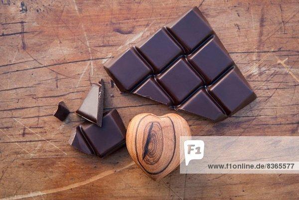 Stilleben mit Zartbitterschokolade und Holzkern