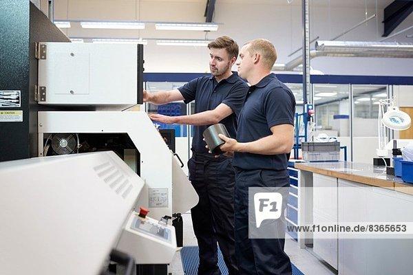 Die Arbeiter kontrollieren das Bedienpult in der Maschinenfabrik