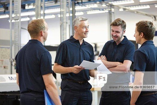 Manager und Arbeiter diskutieren Papierkram in der Maschinenfabrik