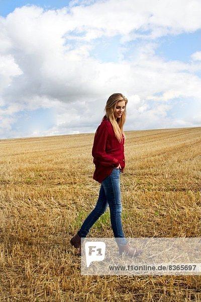 Porträt einer jungen Frau  die auf einem geernteten Feld spazieren geht.