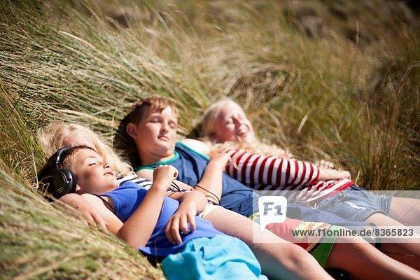 Four friends relaxing in dunes  Wales  UK