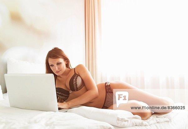 Junge Frau in BH und Slip mit Laptop im Bett