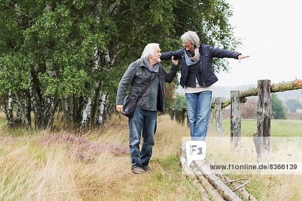 Seniorenpaar  Frau balanciert auf Baumstämmen
