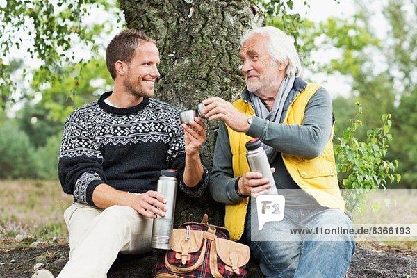 Vater und erwachsener Sohn trinken Kaffee aus der Flasche