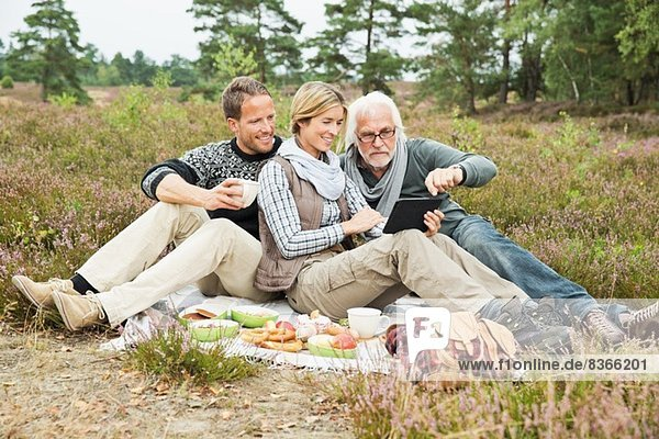 Älterer Mann und mittleres erwachsenes Paar beim Picknick