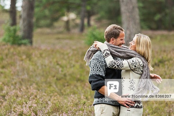 Mid adult couple wrapped in scarf hugging