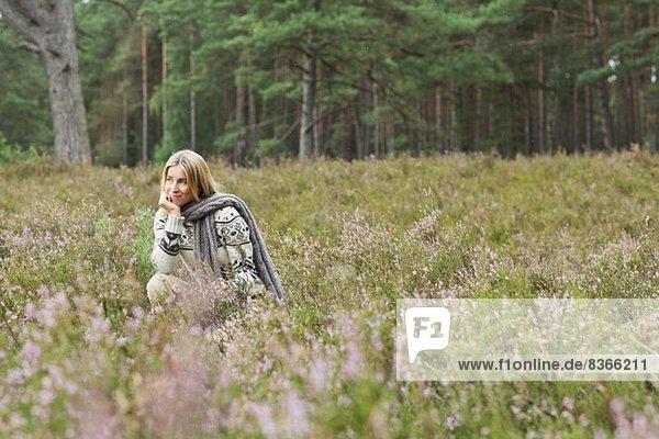 Mittlere erwachsene Frau auf der Wiese mit Hand am Kinn