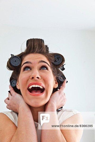 Junge Frau mit Haarrollen  die nach oben schaut.