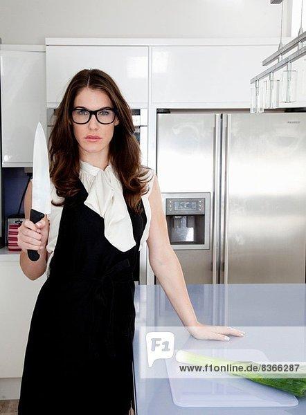 Junge Frau mit Tranchiermesser in der Küche