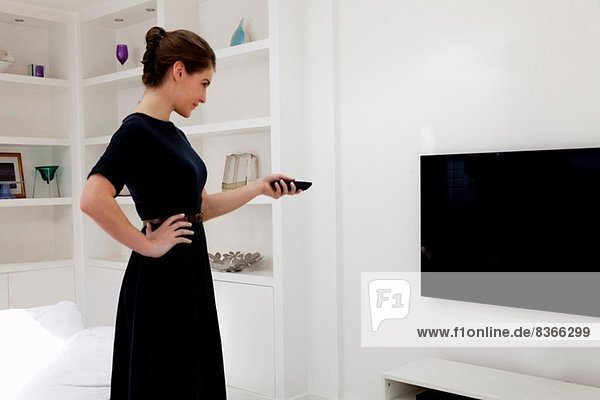 Young woman wearing black dress switching on tv