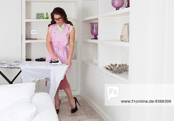 Young woman ironing shirt