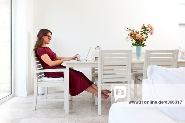 Young woman sitting at table using laptop