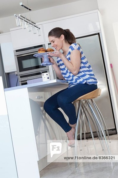 Young woman at breakfast bar smelling freshly baked cakes