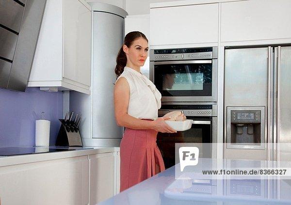 Junge Frau mit Bratschüssel in der Küche