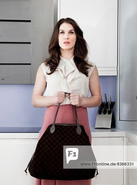 Porträt einer jungen Frau  die eine Handtasche mit leerem Gesichtsausdruck hält.