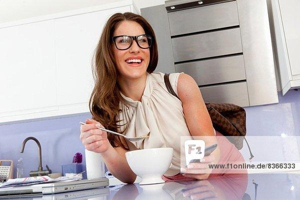 Junge Frau beim Frühstücken mit Handy