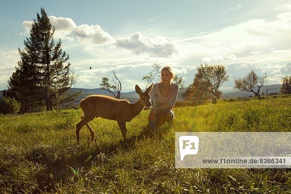 Young woman in field with fawn